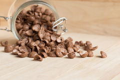 Chocolate cereal cornflakes spilling to the wood surface Royalty Free Stock Image