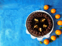 Chocolate cheesecake decorated with mandarins. Chocolate cheesecake decorated with chocolate ganache surrounded by mandarins royalty free stock images