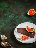 Chocolate cheesecake with fig on green slate background. Royalty Free Stock Image