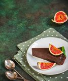 Chocolate cheesecake with fig on green slate background. Stock Image