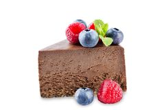 Chocolate cheesecake with fresh berries and mint leaves isolated stock image
