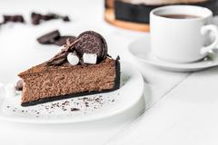Chocolate cheesecake with pieces of chocolate, cookies and marshmallow on a white plate. Next to a cup of tea on the table royalty free stock image