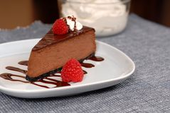 Chocolate cheesecake with raspberries. And chocolate sauce on white plate Stock Photo