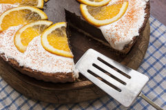 Chocolate cheesecake on a wooden board with metal blade for cake Stock Photos