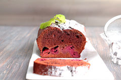 Chocolate and cherry cake frosted with sugar powder on a wooden table with mint leaves Royalty Free Stock Images