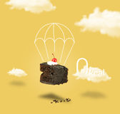 Chocolate cherry cake with parachute on yellow sky back Stock Photos