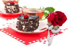 Chocolate cherry cakes, hot tea and red rose Stock Photos