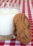 Chocolate chip. Cookie and a glass of milk on red table cloth Royalty Free Stock Photo