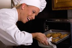 Chocolate Chip Baker. Attractive female Baker taking chocolate chip cookies out of the oven Stock Photos
