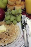 Chocolate Chip Belgian Waffle. Floral plate and silver flatware hold a chocolate chip Belgian waffle with a pad of butter on top.  Waffle is surrounded by fruits Royalty Free Stock Photography
