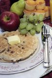 Chocolate Chip Belgian Waffle. Floral plate and silver flatware hold a chocolate chip Belgian waffle with a pad of butter on top.  Waffle is surrounded by fruits Royalty Free Stock Photos