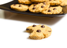 Chocolate chip cookie with a bite and pile of cookies in a plate Royalty Free Stock Photos