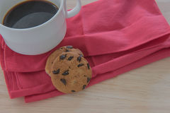 Chocolate chip cookie on a cloth and coffee on wood background. Royalty Free Stock Image