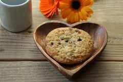 Chocolate chip cookie on the heart-shaped wooden plate with transvaal daisies Stock Photography