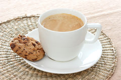 Chocolate chip cookie on saucer with coffee. Close up view of two chocolate chip cookie on white saucer with expresso coffee Royalty Free Stock Photos