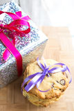 Chocolate chip cookie tied up next to a wrapped up Christmas present. Royalty Free Stock Photography