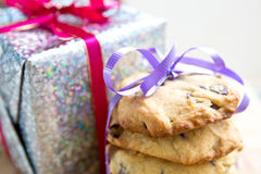 Chocolate chip cookie tied up next to a wrapped up Christmas present. Royalty Free Stock Image