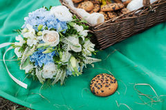 Chocolate chip cookie in wicker basket. Picnic on the grass. Flower arrangement of hydrangea, сakes in a basket Royalty Free Stock Image