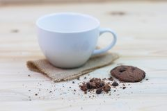 Chocolate chip cookies with a bite mark and a cup placed on a sa. Ck on a wooden table royalty free stock image