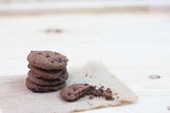 Chocolate chip cookies with a bite mark placed on a sack on a wo. Oden table royalty free stock photos