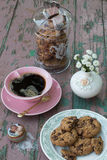 Chocolate Chip Cookies, Black Coffee and Flowers. Chocolate Chip Cookies on a Plate, a Glass Cookie Jar, a Cup of Black Coffee, Tiny White Flowers in a Porcelain Royalty Free Stock Photography