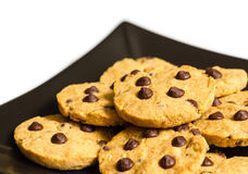 Chocolate chip cookies on a black plate isolated on white backgr Royalty Free Stock Image