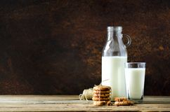 Chocolate chip cookies, bottle and glass of milk on wooden table, dark background. Sunny morning, copy space Stock Photos