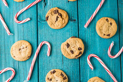 Chocolate Chip Cookies & Christmas Candy Canes. Freshly Baked Chocolate Chip Cookies out of the oven & Christmas Candy Canes - spread out on vintage blue wood Royalty Free Stock Photo