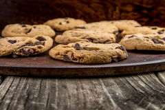 Chocolate Chip Cookies. Freshly Baked Chocolate Chip Cookies out of the oven - cookies on cooking sheet on vintage wood table background Royalty Free Stock Image