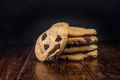 Chocolate Chip Cookies. Freshly Baked Chocolate Chip Cookies out of the oven - stack of cookies on shiny hardwood table surface and black background Stock Images