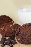Chocolate Chip Cookies with Glass of Milk. Chocolate chip cookies with a glass of milk and chocolate pieces on a beige background with a shallow DOF Stock Photo