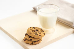 Chocolate chip cookies and a glass of milk on plate. Chocolate chip cookies and a glass of milk on wooden plate Royalty Free Stock Image