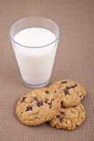 Chocolate chip cookies and milk. Chocolate chip cookies and a glass of milk, on a brown cotton tablecloth Stock Images