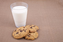 Chocolate chip cookies and milk. Chocolate chip cookies and a glass of milk, on a brown cotton tablecloth Royalty Free Stock Photo