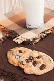 Chocolate chip cookies and milk. Two chocolate chip cookies served with a glass of milk. Shallow DOF and focus is on the cookies Royalty Free Stock Images