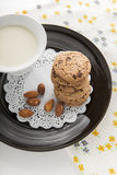 Chocolate chip cookies. With milk in cup on black dish Stock Images