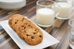 Chocolate chip cookies and milk on dark wood table. Chocolate chip cookies on rectangular plate and glass of milk on dark wood pattern table. Selective focus on Royalty Free Stock Image