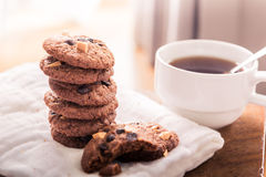 Chocolate chip cookies on napkin and hot tea on wooden table. Royalty Free Stock Photography
