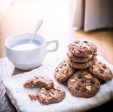 Chocolate chip cookies on napkin and hot tea on wooden table. Stock Photos
