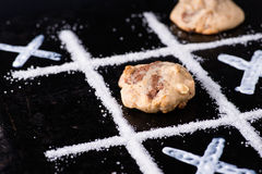 Chocolate chip cookies on noughts and crosses sugar grid. Dark background, creative image, closeup, selective focus Stock Photo