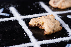Chocolate chip cookies on noughts and crosses sugar grid. Dark background, creative image, closeup, selective focus Royalty Free Stock Images