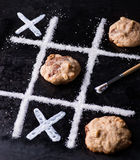 Chocolate chip cookies on noughts and crosses sugar grid. Dark background, creative image, selective focus Royalty Free Stock Photos