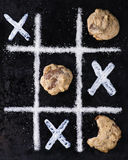 Chocolate chip cookies on noughts and crosses sugar grid. Dark background, creative image, selective focus Stock Photos