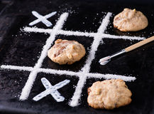 Chocolate chip cookies on noughts and crosses sugar grid. Dark background, creative image, selective focus Royalty Free Stock Photography