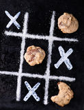 Chocolate chip cookies on noughts and crosses sugar grid. Dark background, creative image, top view Stock Image