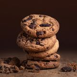 Chocolate chip cookies on old wooden table. Stacked Chocolate cookies on dark background, closeup stock photo