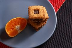Chocolate chip cookies and piece of orange on plate and on red and black background with place for text selective focus with copys. Chocolate chip cookies and Stock Photo