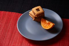 Chocolate chip cookies and piece of orange on plate and on red and black background with place for text selective focus with copys. Chocolate chip cookies and Stock Photos