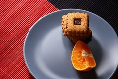 Chocolate chip cookies and piece of orange on plate and on red and black background with place for text selective focus with copys. Chocolate chip cookies and Royalty Free Stock Photo