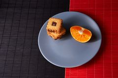 Chocolate chip cookies and piece of orange on plate and on red and black background with place for text selective focus with copys. Chocolate chip cookies and Royalty Free Stock Photos
